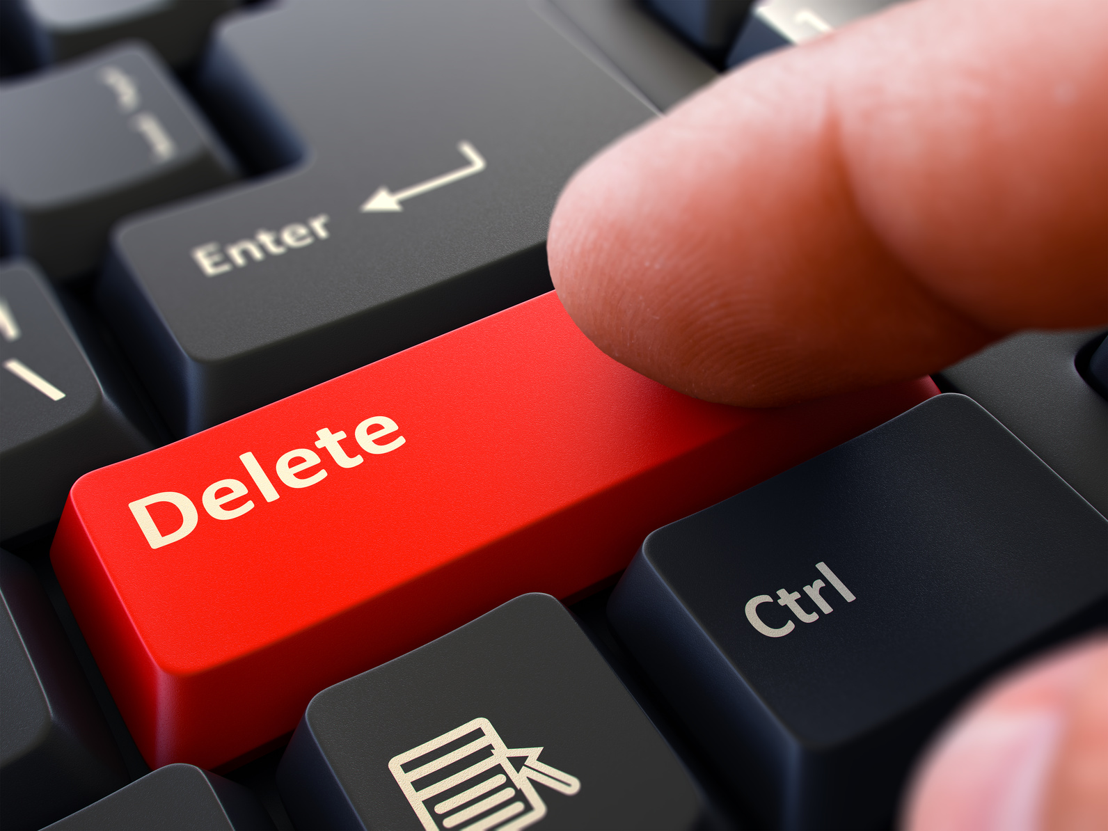 Delete - Written on Red Keyboard Key. Male Hand Presses Button on Black PC Keyboard. Closeup View. Blurred Background.